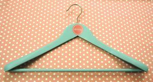 Emmy Dress-hanger. Light green wood with printed logo